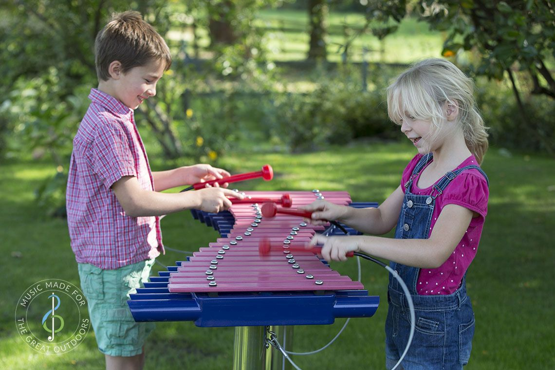 Boy and girl standing on opposite sides and playing a large blue outdoor xylophone with red beaters
