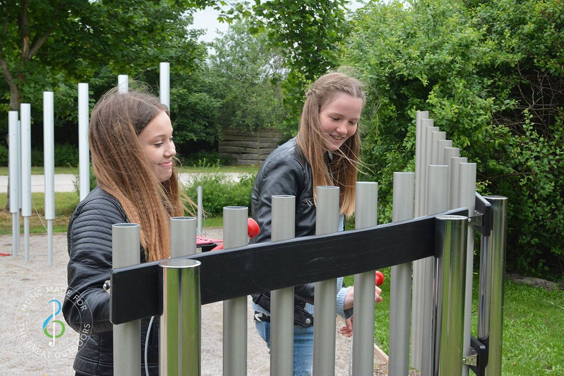 teenage girls in music park playing on outdoor musical chimes