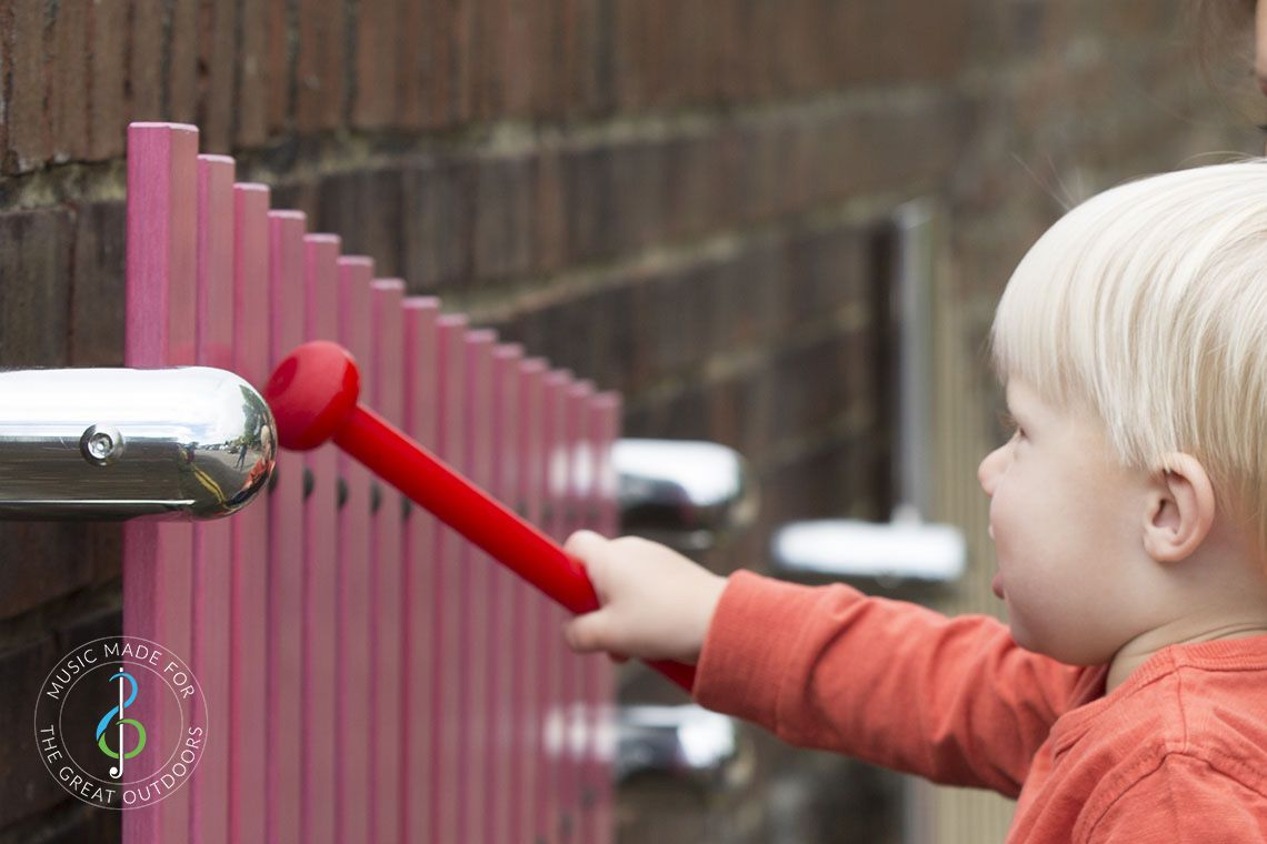 close up of blonde baby hitting pink wall mounted xylophone with a red beater