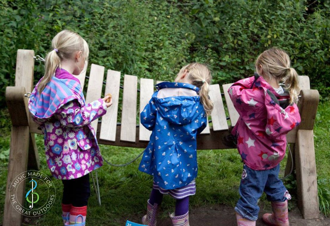 Three Young Girls in Raincoats Playing Large Outdoor Akadinda Xylophone