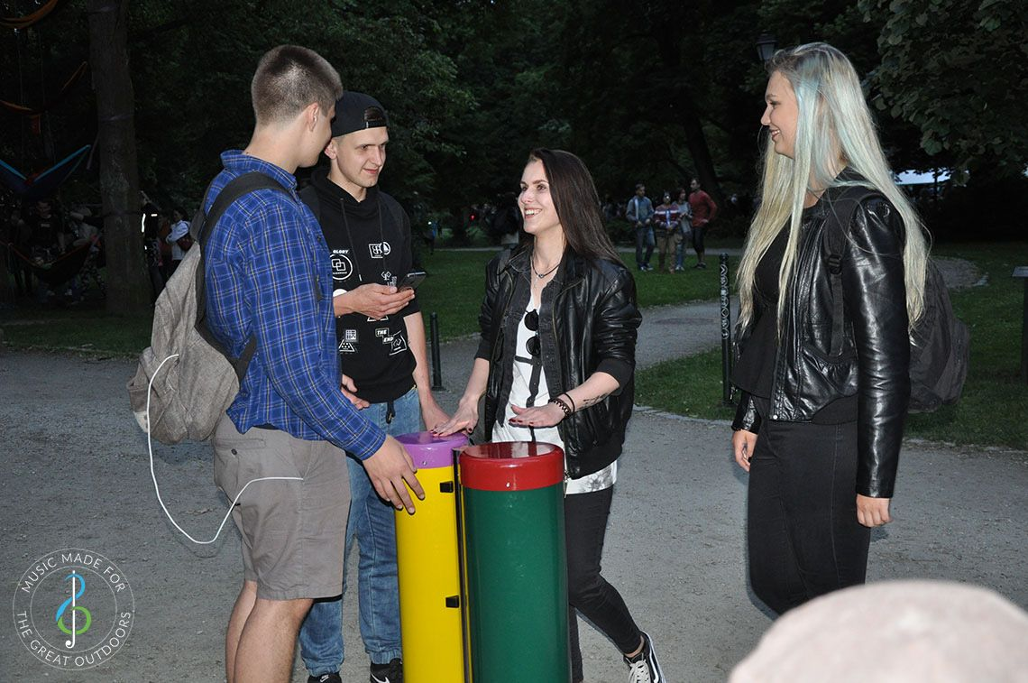 Four older teenagers laughing and playing pair of conga drums in music playground at dusk