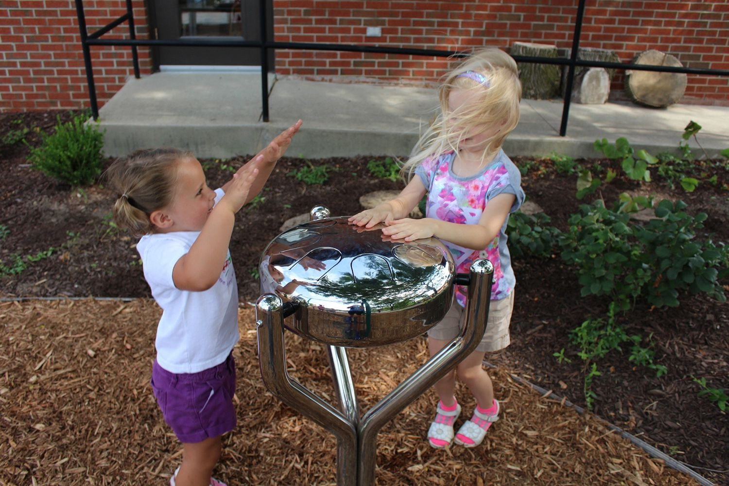 two little girls Playing Stainless Steel drum in playground