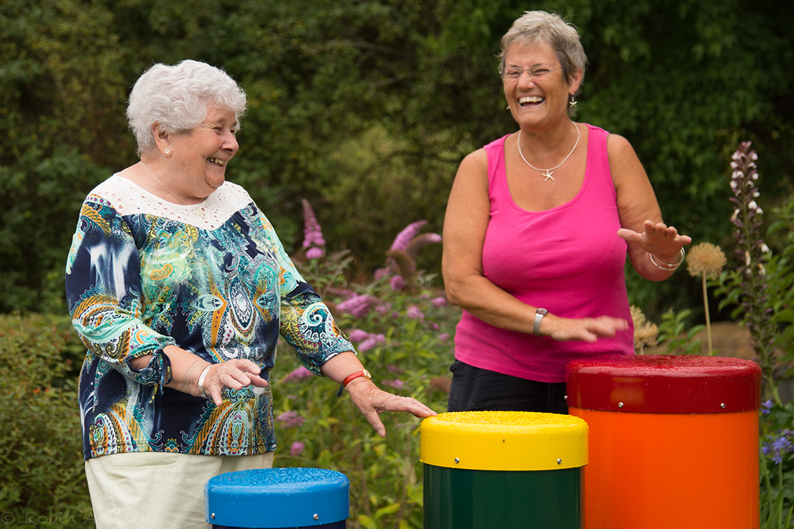 two older ladies playing a colourful set of 5 outdoor samba drums in a park