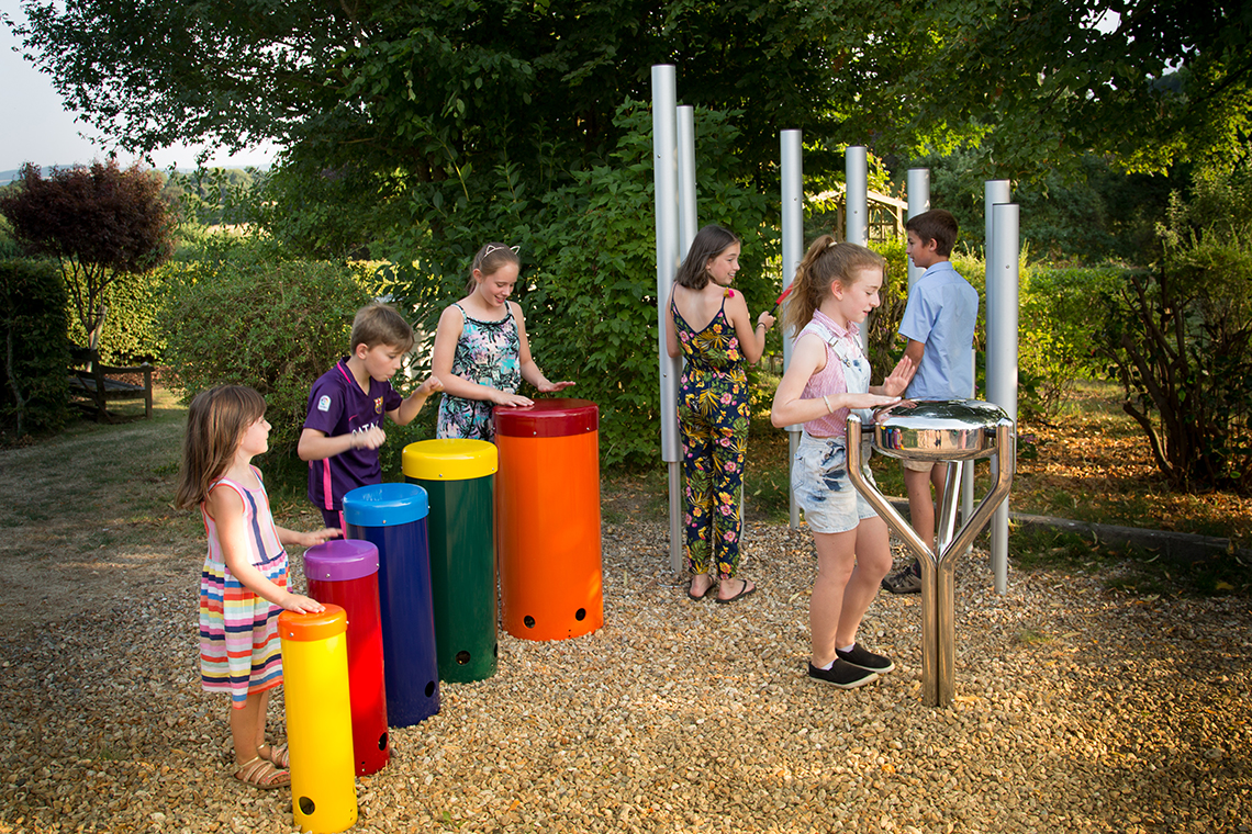 group of six children playing on an ensemble of outdoor musical instruments in a park