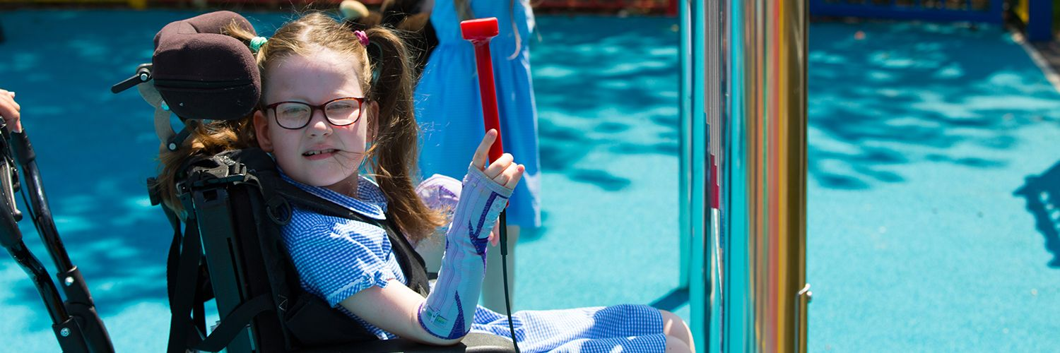 Little girl in a wheelchair playing an outdoor musical instrument in her school playground