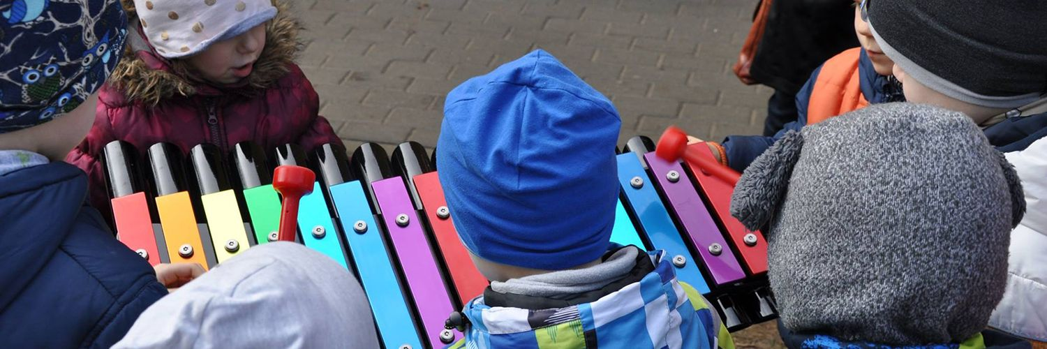 lots of little children in woolly hats surrounding a colourful outdoor xylophone in a playground