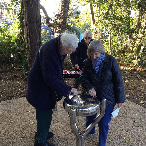 two ladies playing a round stainless steel tongue drum in the Aldeburgh Hopsital sensory garden