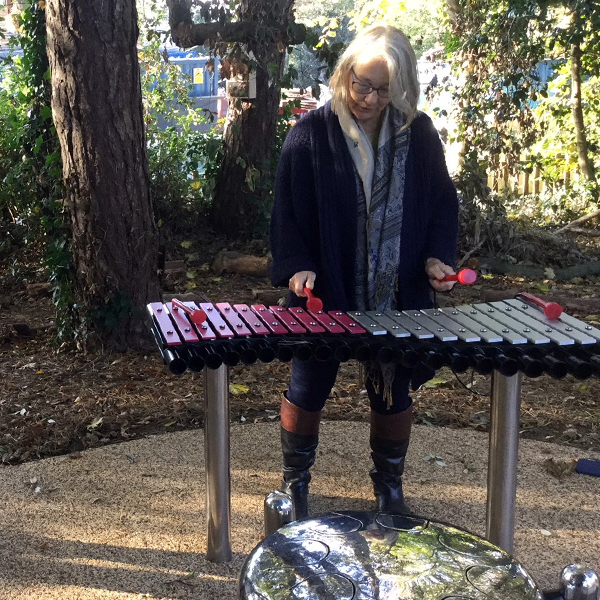 lady with grey hair playing a pin and silver large outdoor xylophone in the Aldeburgh hospital Sensory Garden