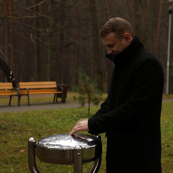 man in a park standing playing a large metal tongue drum