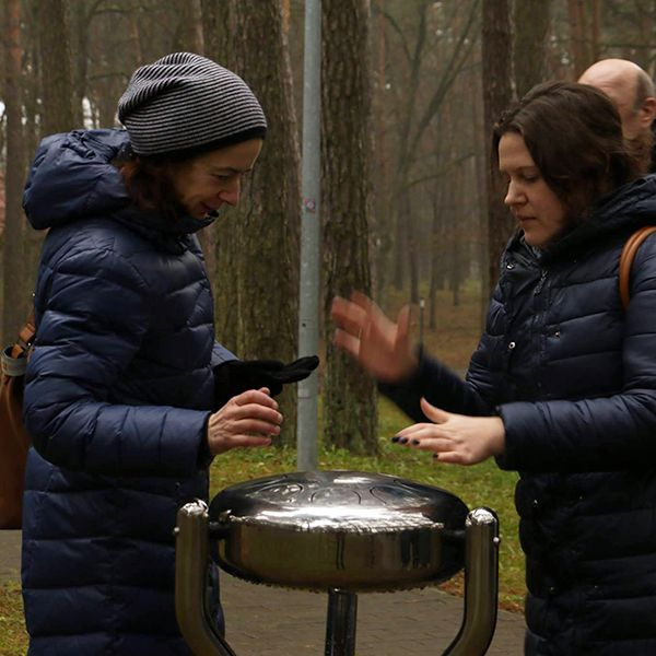 Two ladies playing a stainless steel tongue drum in a city park