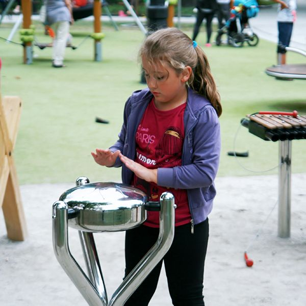 girl playing a round stainless steel tongue drum in a busy park