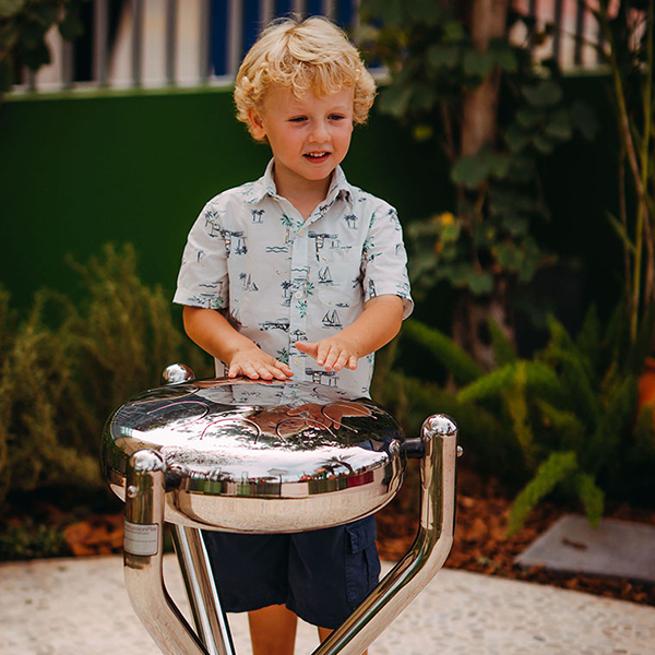 Small blonde boy playing an outdoor stainless steel tongue drum in a music park