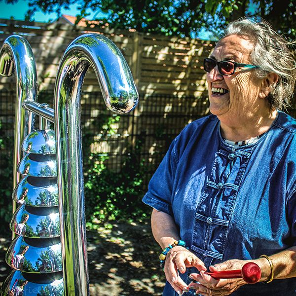 older lady playing a bell lyre outdoor instrument in the sunshine