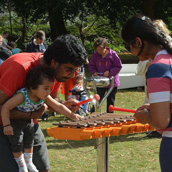 Parents with Father holding a baby playing an orange xylophone in a park