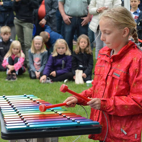 school girl playing colourful outdoor xylophone in a school playground