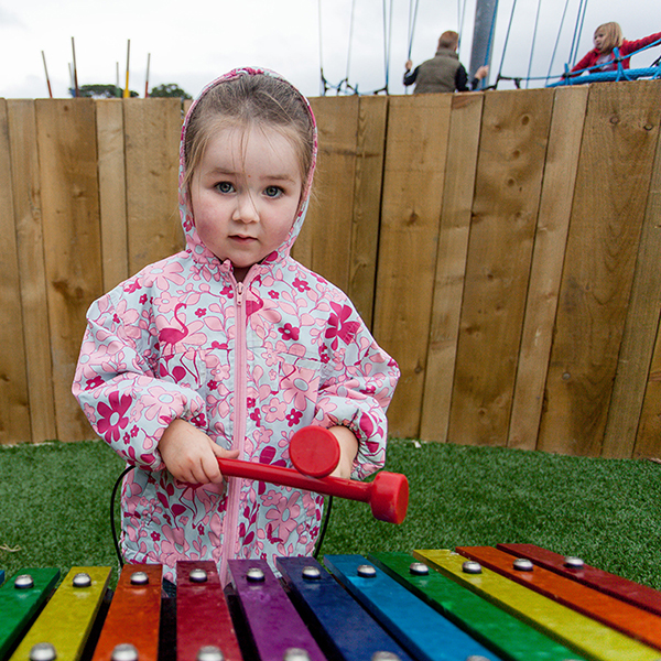 little girl playing a large outdoor musical instrument in the new playground at Greystones Co Wicklow Ireland
