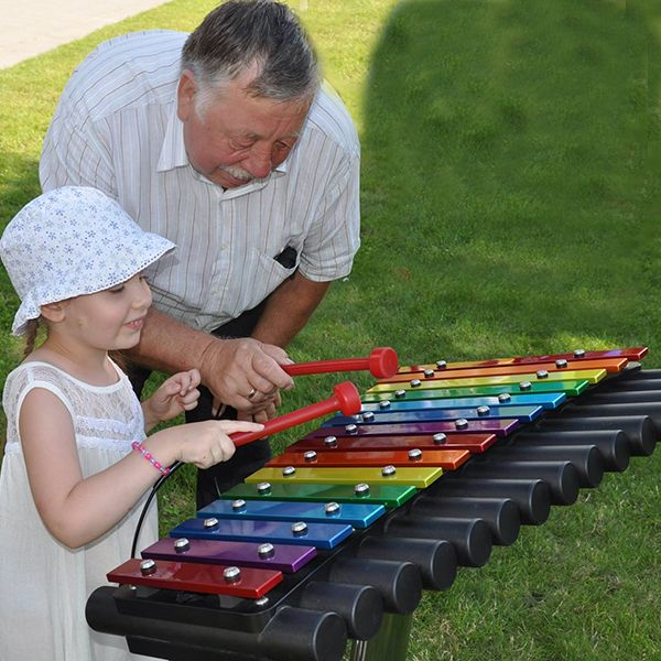 Rainbow Coloured Outdoor Xylophone in Park being played by a small girl with her grandad watching