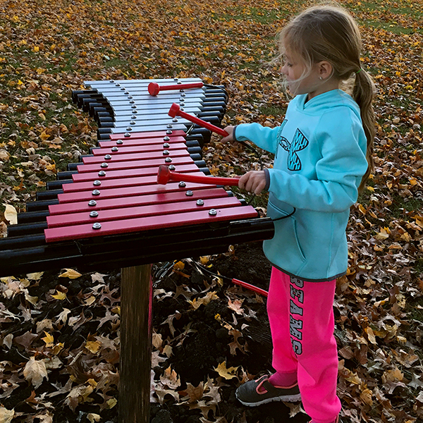 Little girl playing a large outdoor xylophone in Anderson Park City of Essex