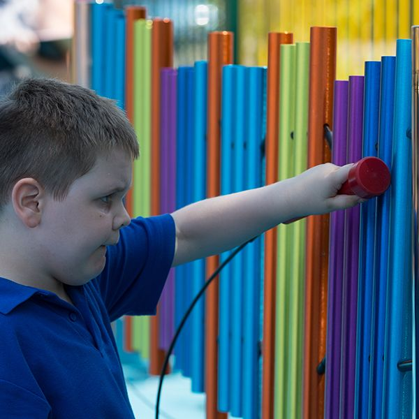 boy with special needs playing rainbow coloured chimes outdoors
