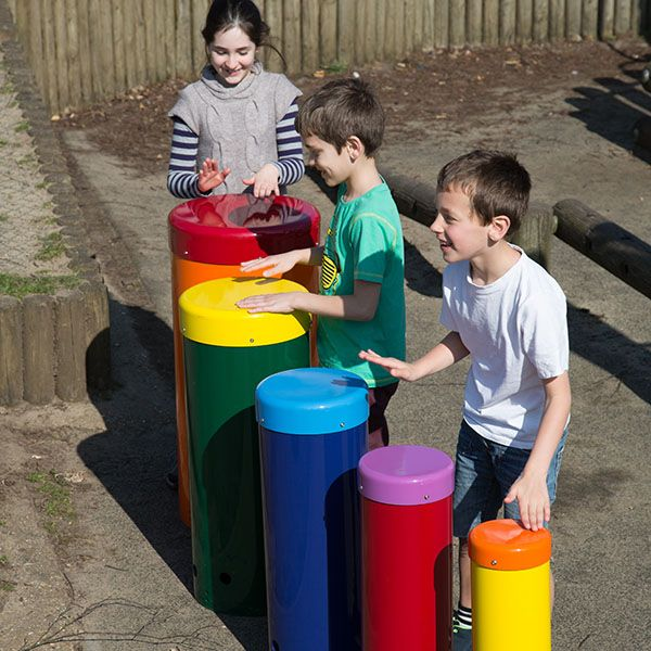 three children playing on a set of five rainbow coloured drums in a playground