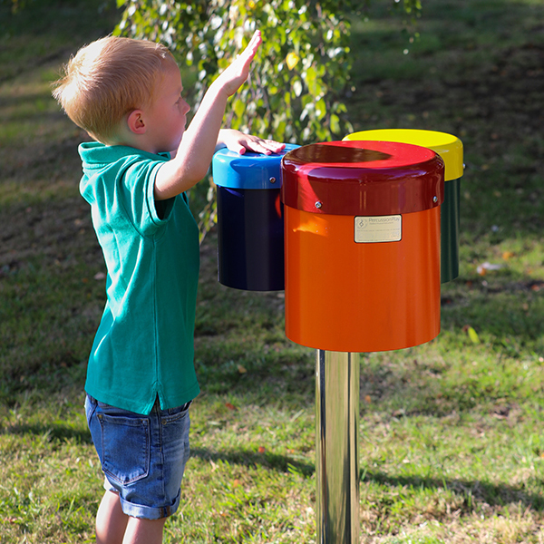 small boy reaching up and playing a colourful set of three outdoor drums mounted on a single post in a park