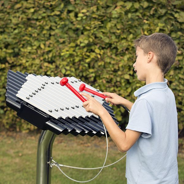 Schoolboy playing  a silver outdoor xylophone in a playground