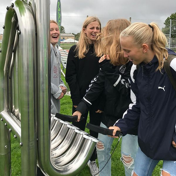 Group of teenage girls in a playground laughing and hitting a large silver outdoor musical instrument with five tall pipes