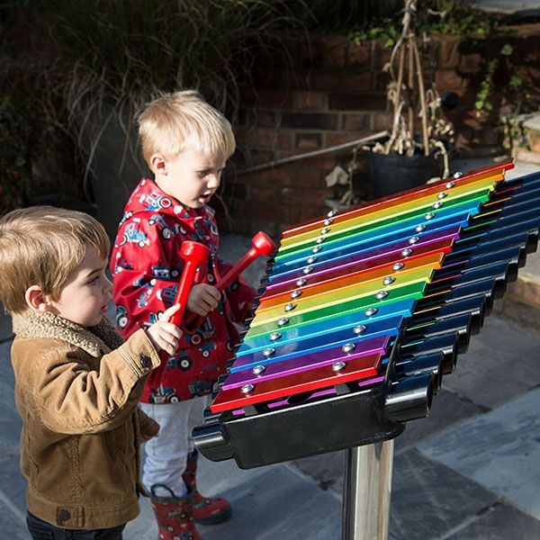 two little boys playing a large rainbow coloured xylophone in a playground
