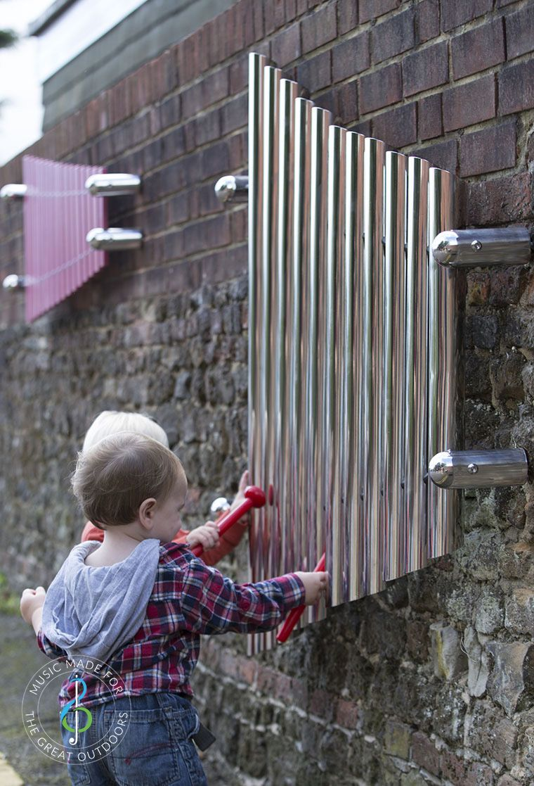 two toddlers stood playing large mirrored wall chimes with red beaters
