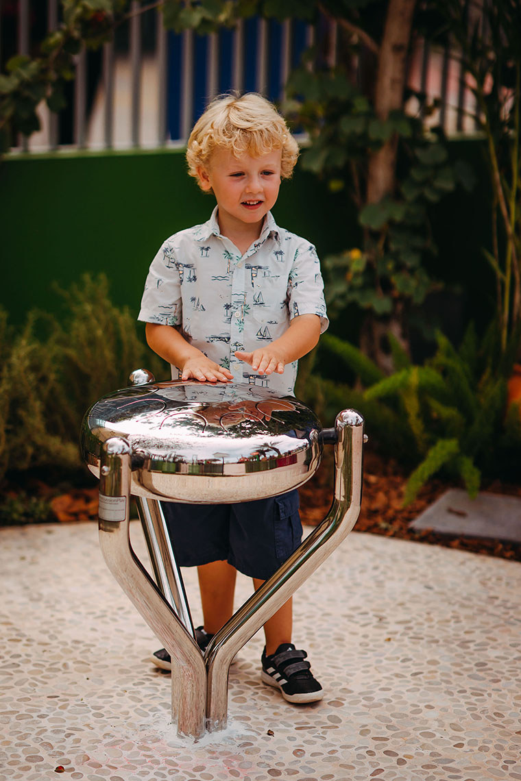 A blonde little boy playing a stainless steel tongue drum in a music park or playground