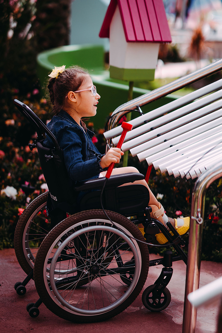 a young girl with special needs and in a wheelchair smiling and playing a large metal outdoor musical instrument in a playground