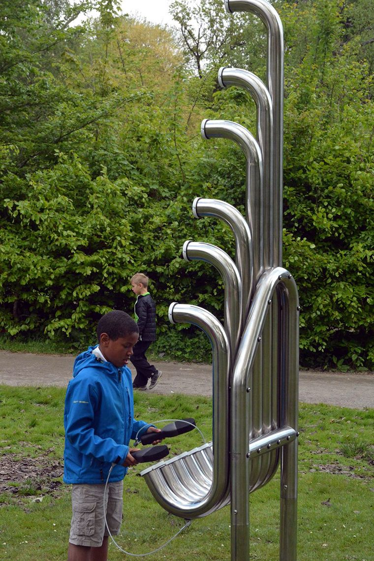 Black boy in a park playing huge silver outdoor musical instrument