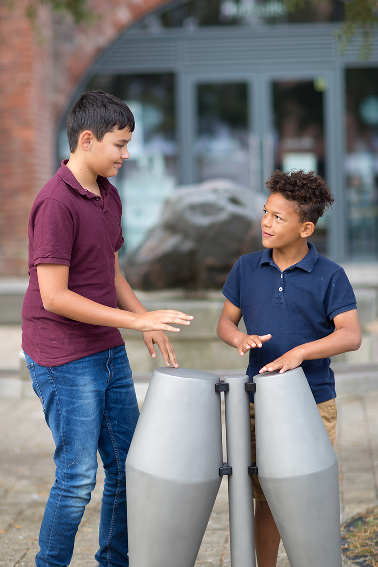 two brothers playing on a pair of outdoor Tumbadora drums in a street