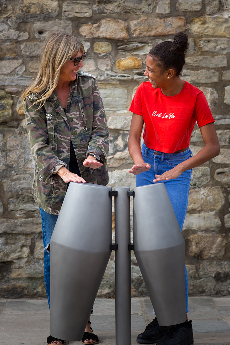 a mum and daughter playing a pair of tumbadora outdoor drums in the street together