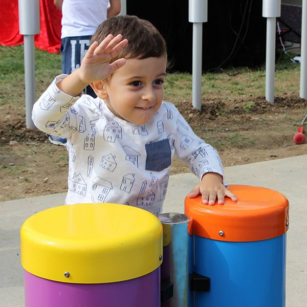 Young Boy Smiling Playing Outdoor Conga Drums