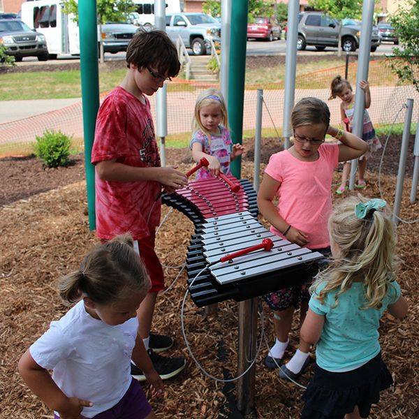 Group of children gathered around a large outdoor xylophone in school yard