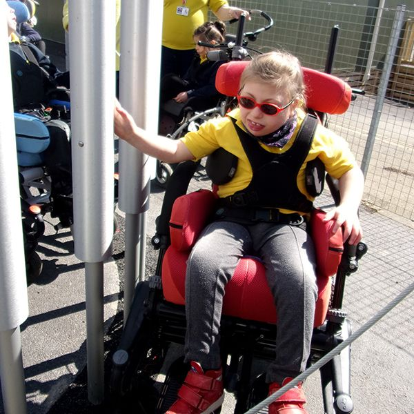 girl in wheelchair reaching out and touching large tubular bell in school playground