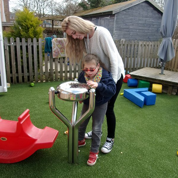 young girl and her carer playing a stainless steel outdoor tongue drum together in special needs school playground