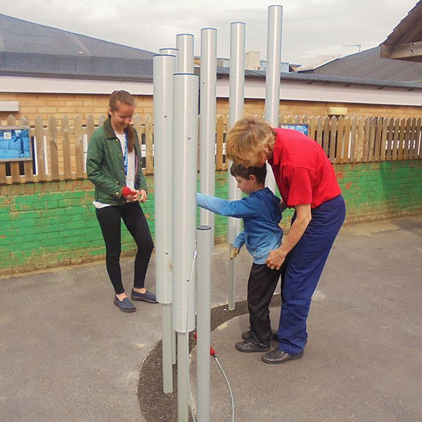 young boy and his carer playing large outdoor tubular bells together in special needs school playground