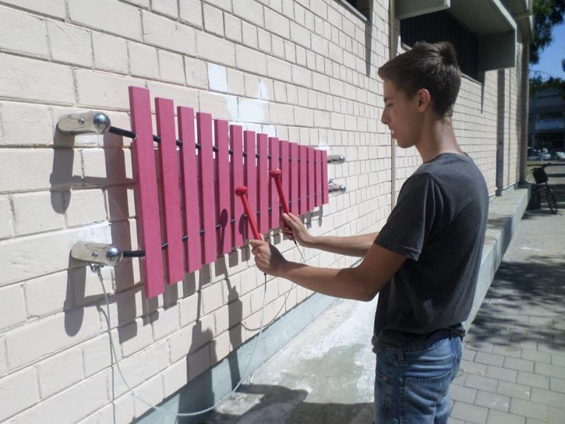 boy playing wall mounted marimba xylophone outside Tel Aviv Music Centre