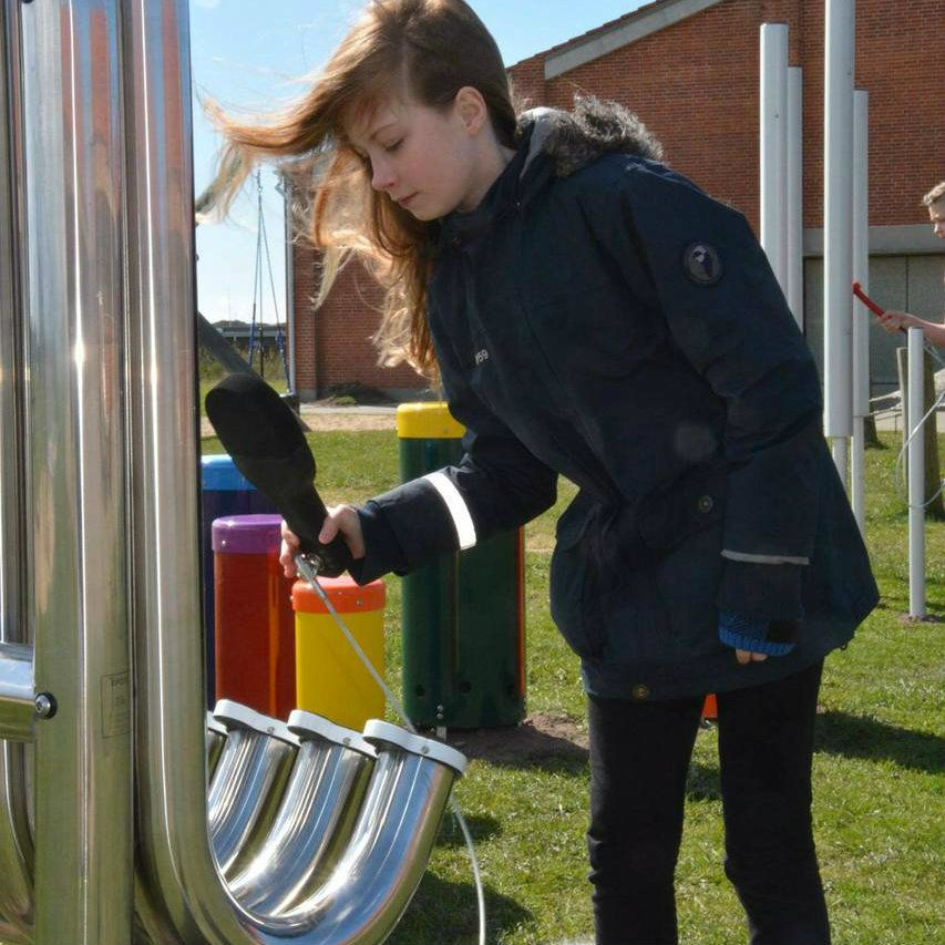 girl hitting large silver outdoor aerophones or slap tubes in school playground