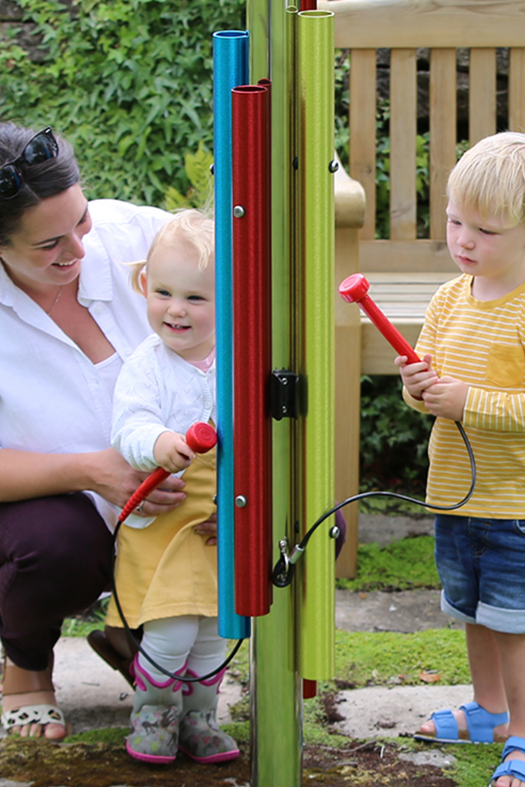 Mother and two children playing a post of musical instruments in a musical playground