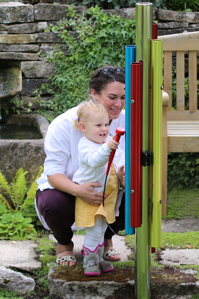 mother and child playing an outdoor musical instrument with four colorful chimes and red mallet