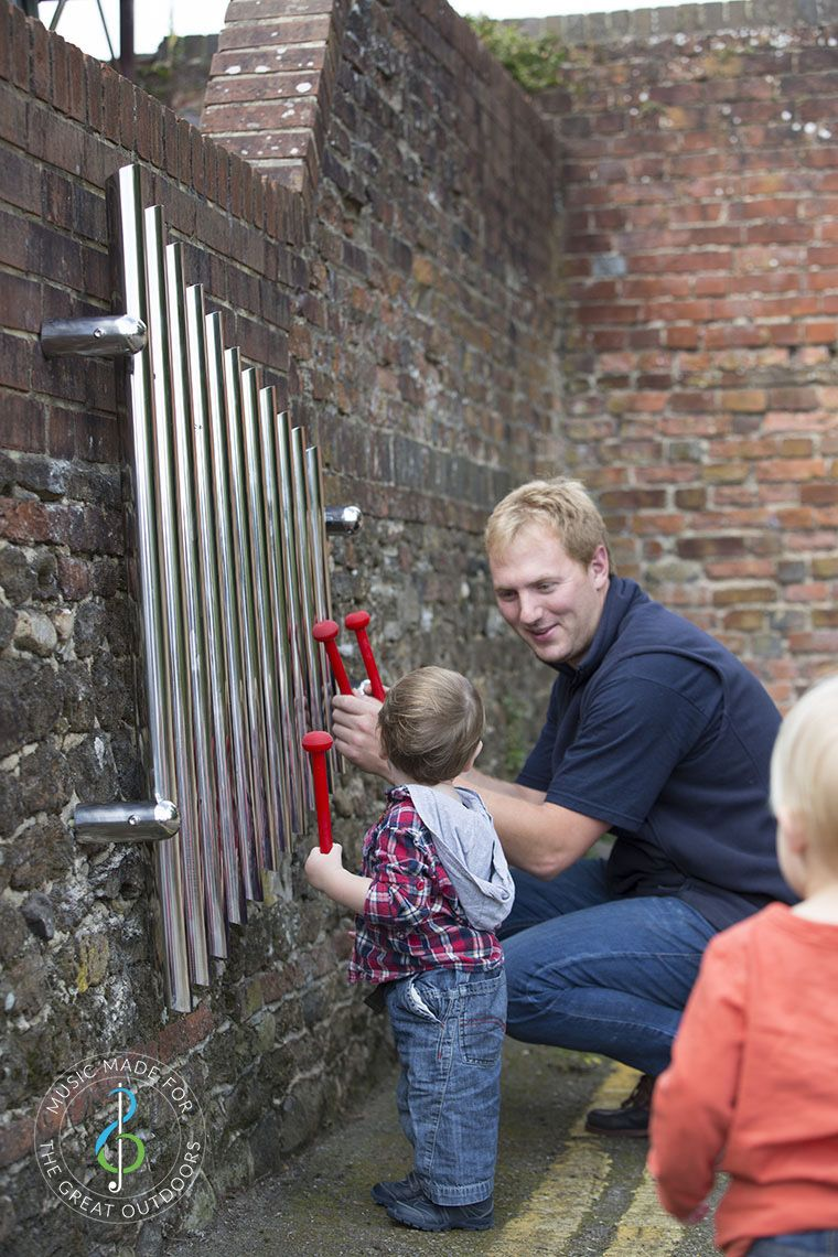 man and baby playing wall mounted mirrored chimes together