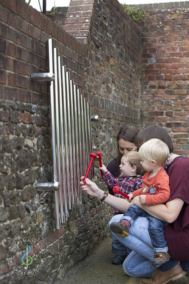 mother and child playing mirrored wall chimes together