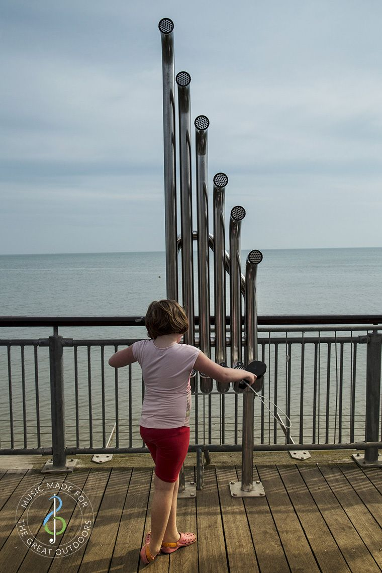 back of girl hitting large silver outdoor aerophones or slap tubes on the end of a pier looking out to sea