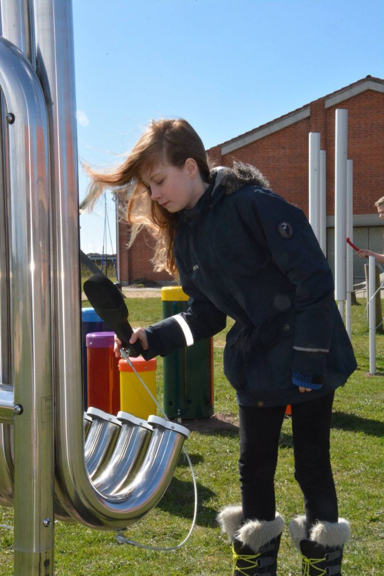 Girl hitting pipes of a large Aerophones with a black paddle in a School Playground