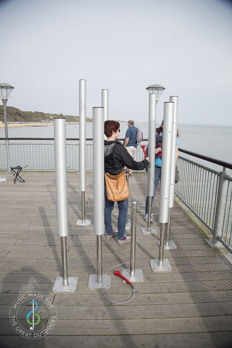 woman playing large upright silver musical chimes on end of pier