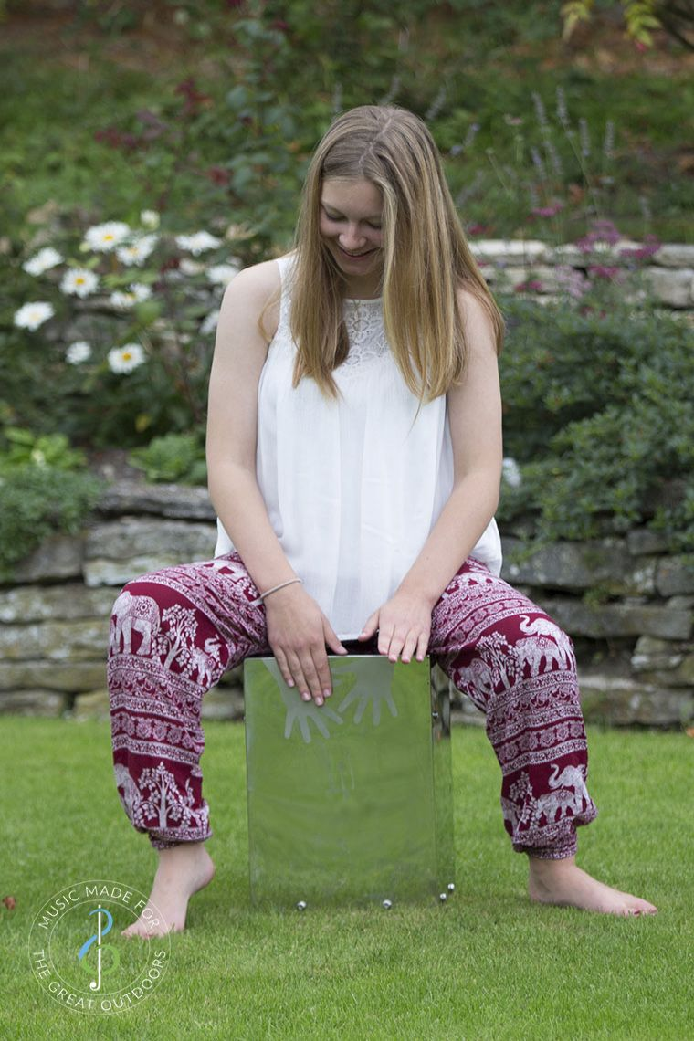 Teenage Girl Playing Stainless Steel Cajon Drum in Garden