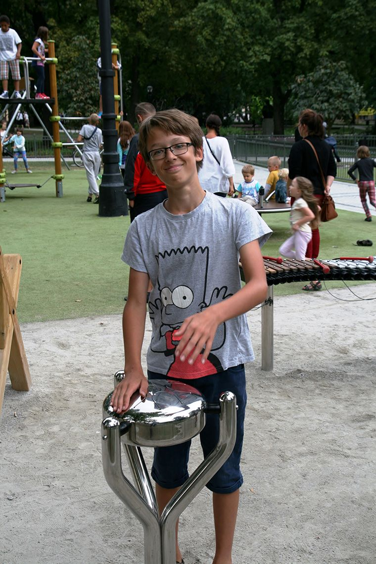 young man playing a stainless steel tongue drum in a busy playground